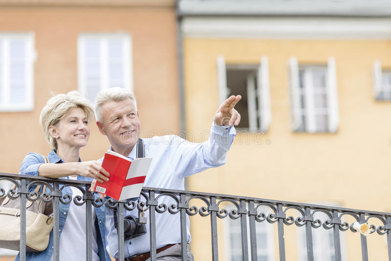 Glücklicher Mann, der der Frau mit Führer etwas in der Stadt zeigt stockbild