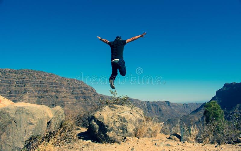Glücklicher Mann, der in die Bergspitze springt stockbild