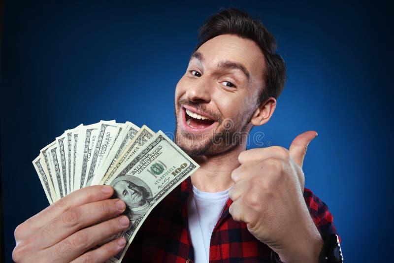 Glücklicher Mann, der 100 Dollarscheingeld in seiner Hand hält stockfotos