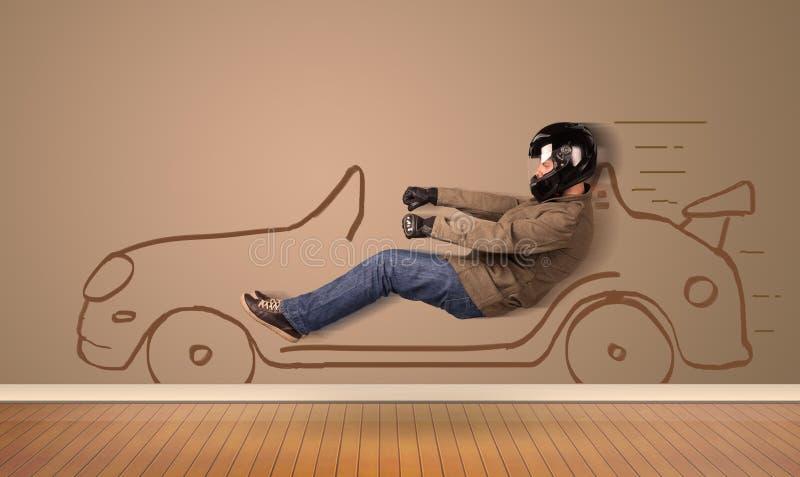 Glücklicher Mann, der ein Hand gezeichnetes Auto auf der Wand fährt stockbild