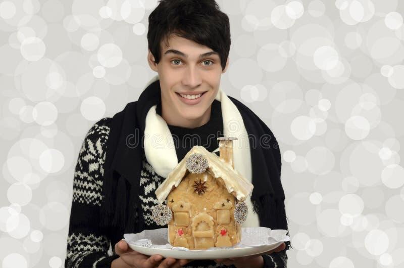 Glücklicher Mann, der ein Lebkuchenhaus hält stockfoto
