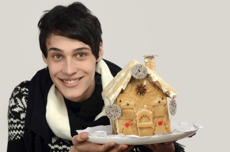 Glücklicher Mann, der ein Lebkuchenhaus hält lizenzfreie stockbilder