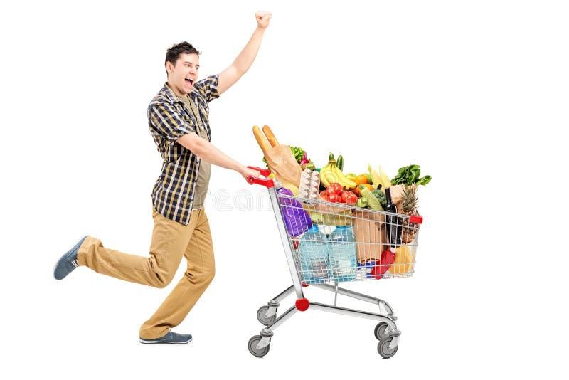 Glücklicher Mann, der einen Einkaufswagen drückt stockfoto