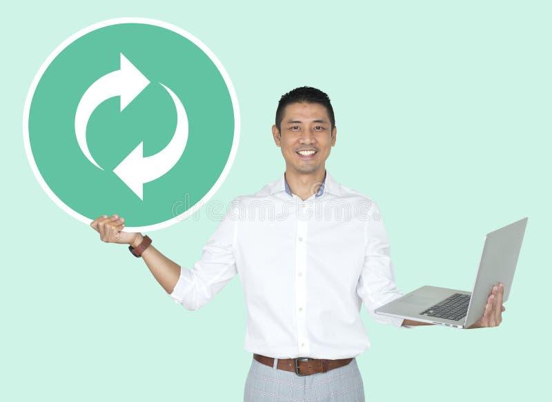 Glücklicher Mann, der einen Laptop und hält, Ikone zu erneuern stockfoto