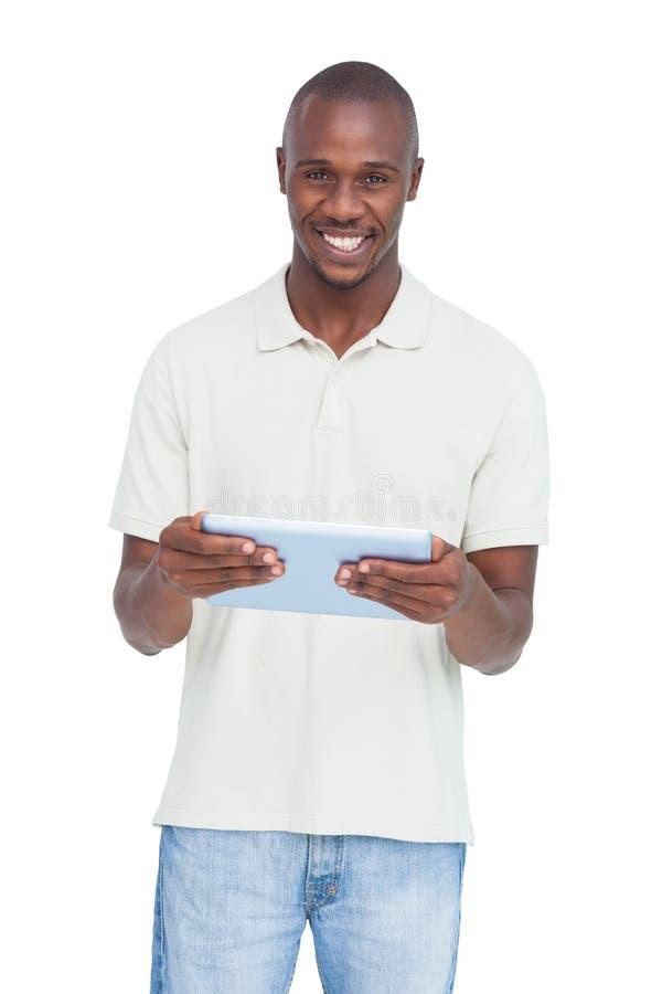 Glücklicher Mann, der einen Tabletten-PC hält stockfoto