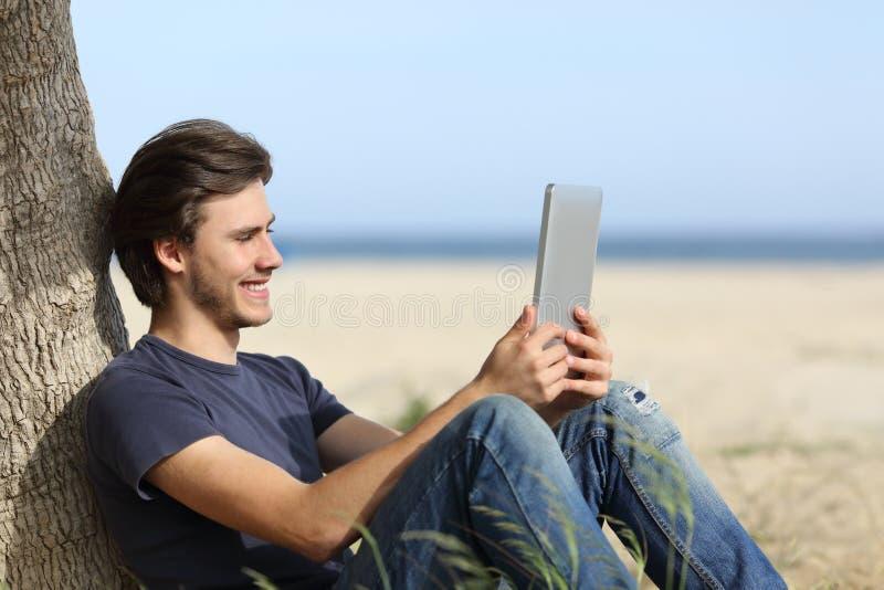 Glücklicher Mann, der einen Tablettenleser sitzt auf dem Strand liest lizenzfreies stockfoto