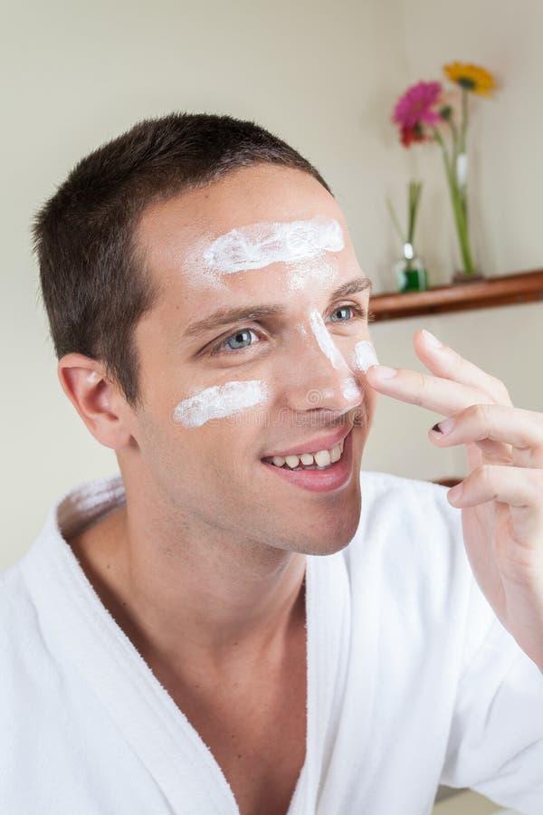 Glücklicher Mann, der Gesichtscreme aufträgt stockbild
