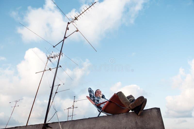 Glücklicher Mann, der im Stuhl am Rand des Dachs in der Stadt stillsteht lizenzfreies stockbild