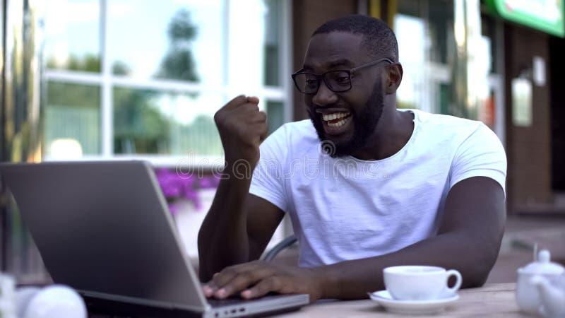 Glücklicher Mann, der ja Geste tut und den Laptop oben empfängt Finanzierung nach Anfang betrachtet lizenzfreies stockbild