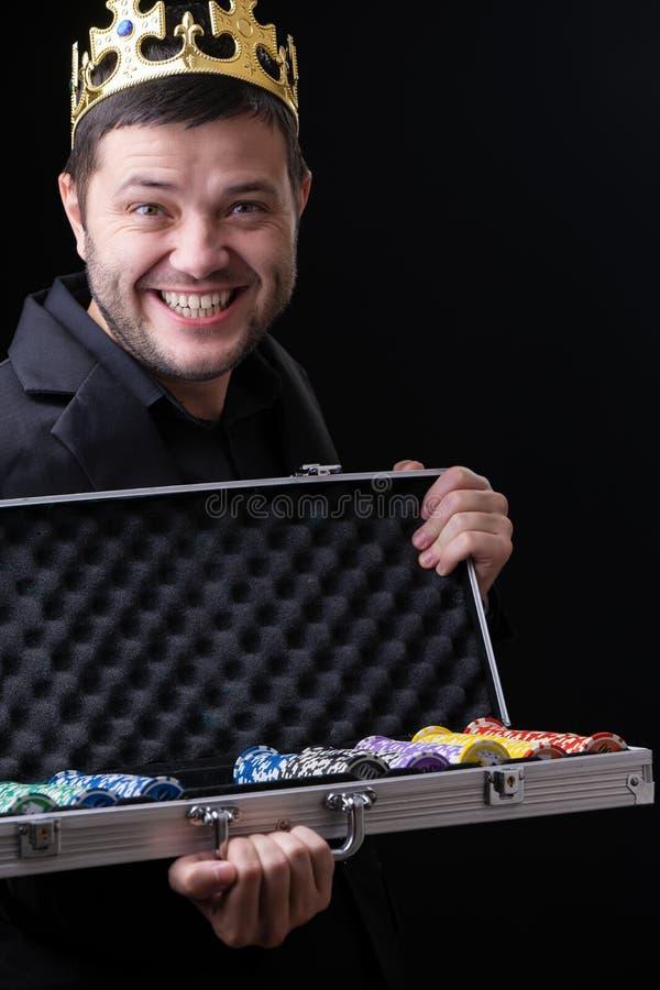 Glücklicher Mann in der Krone mit Koffer mit Chips stockfotos