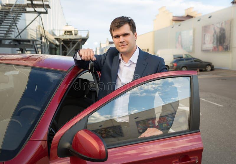 Glücklicher Mann, der mit Neuwagen aufwirft und Schlüssel zeigt stockfoto