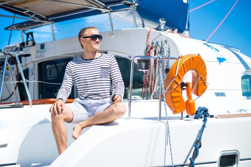 Glücklicher Mann in der modernen Kleidung auf einem Boot stockfoto