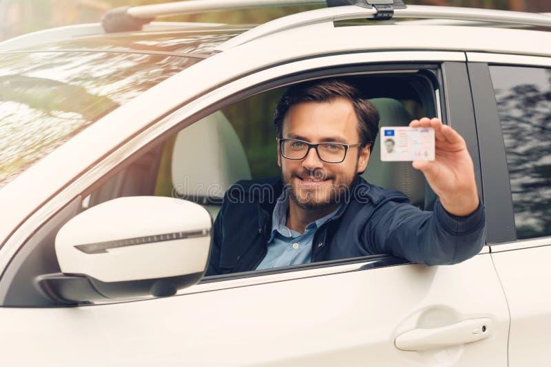 Glücklicher Mann, der seinen neuen Führerschein zeigt lizenzfreies stockfoto