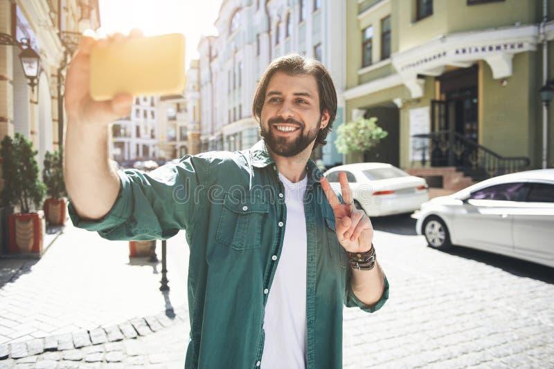 Glücklicher Mann, der selfie im Marktplatz macht stockfotografie