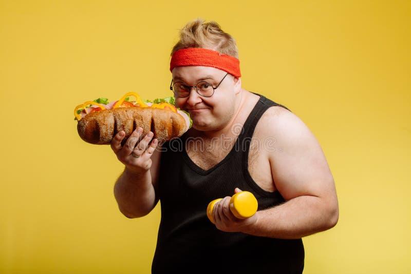 Glücklicher Mann, der sich vorbereitet, Burger zu essen und Kamera zu betrachten stockbilder