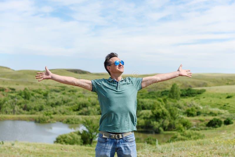 Glücklicher Mann in der Sonnenbrille steht im Wind und untersucht den Himmel Arme werden heraus verbreitet Freiheit lizenzfreies stockfoto
