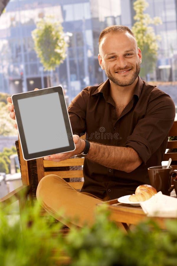 Glücklicher Mann, der Tablette mit leerem Bildschirm hält lizenzfreie stockfotografie