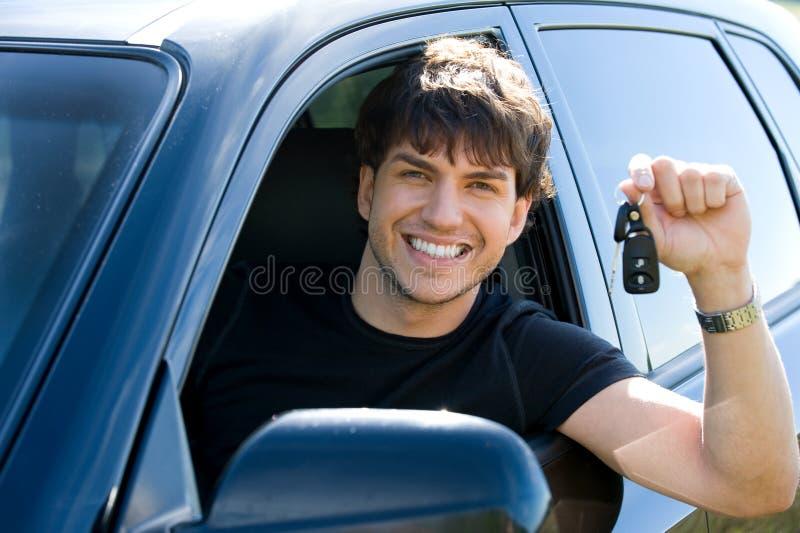 Glücklicher Mann, der Tasten im Auto zeigt lizenzfreie stockbilder
