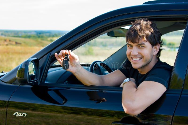 Glücklicher Mann, der Tasten vom Auto zeigt lizenzfreie stockfotografie