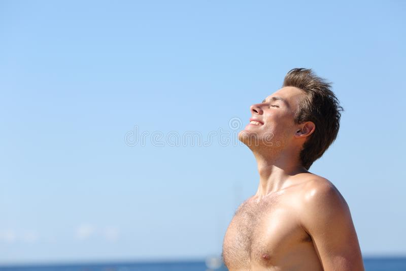 Glücklicher Mann, der tief Frischluft auf dem Strand atmet stockfoto