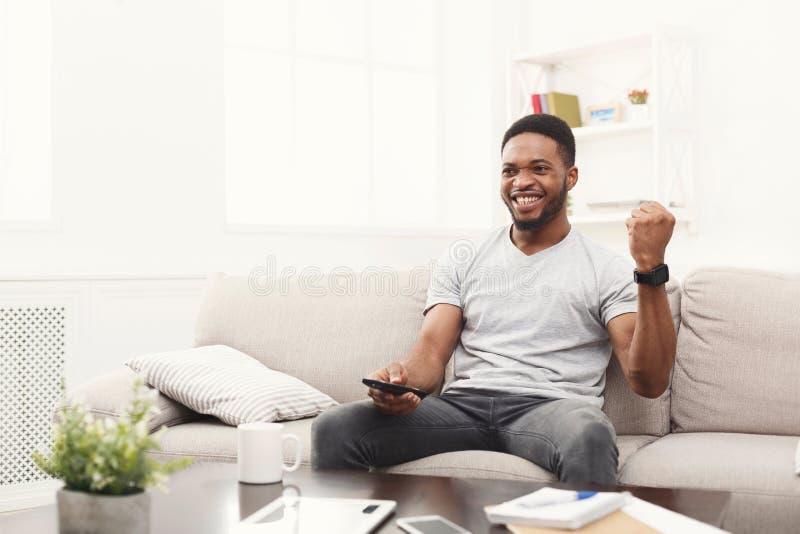 Glücklicher Mann, der unter Verwendung des Fernprüfers im Wohnzimmer fernsieht stockbilder