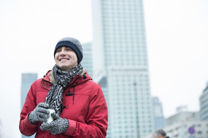 Glücklicher Mann in der warmen Kleidung, die draußen Wegwerfschale hält lizenzfreie stockfotografie