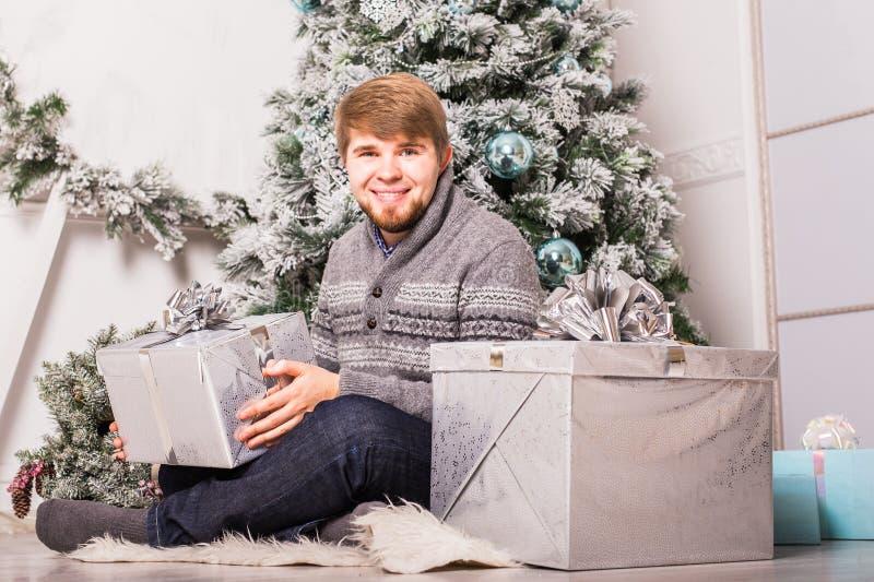 Glücklicher Mann, der zu Hause ein Geschenk nahe Weihnachtsbaum öffnet lizenzfreie stockbilder