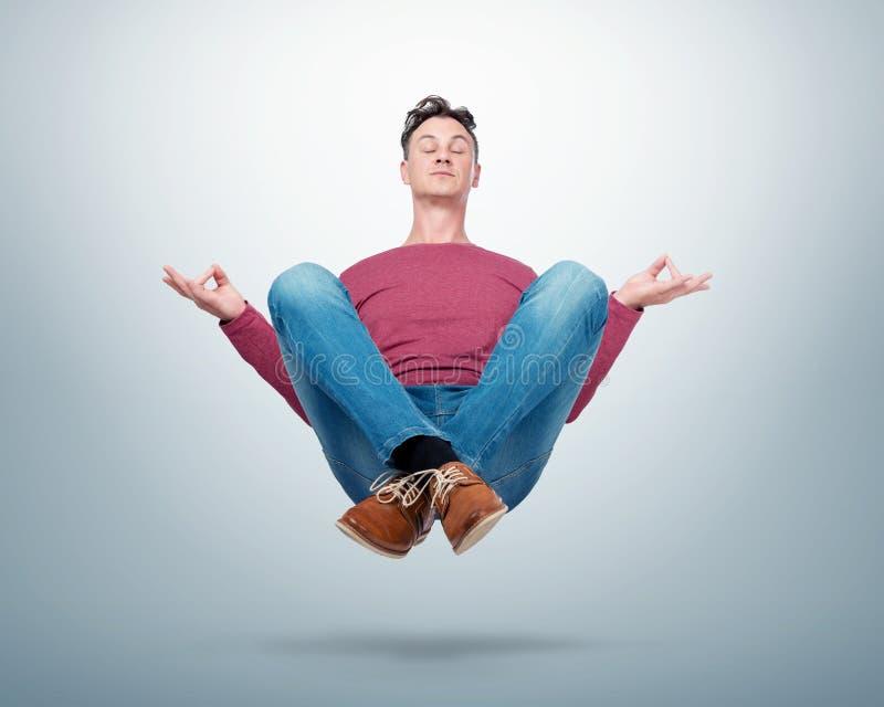 Glücklicher Mann in der zufälligen Kleidung, die sein meditierendes Frei schweben der Augen in der Luft schließt stockfotos
