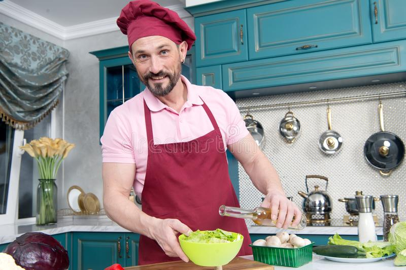 Glücklicher Mann fügt Öl in frischen Salat hinzu Bärtiger gelächelter Chef, der Olivenöl in Gemüsesalat hinzufügt lizenzfreies stockbild