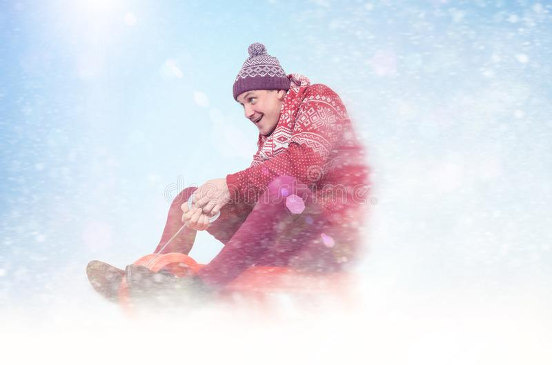 Glücklicher Mann im roten Strickjacken- und Hutrodeln Winter, Sonne, Schnee, erweitert sich stockbild