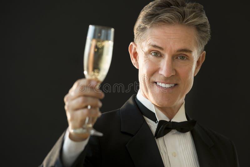 Glücklicher Mann im Smoking, das Champagne Flute hält stockfoto