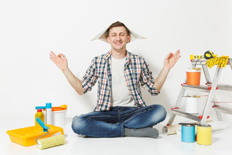 Glücklicher Mann im Zeitungshut, der auf Boden meditierend, das Yoga tuend sitzt und entspannen sich mit Instrumenten für Erneuer lizenzfreies stockfoto