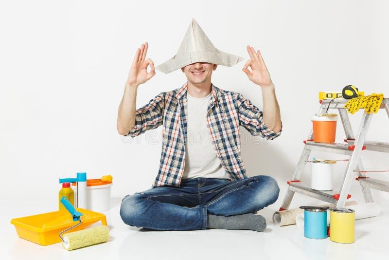Glücklicher Mann im Zeitungshut, der auf Boden meditierend, das Yoga tuend sitzt und entspannen sich mit Instrumenten für Erneuer stockbild