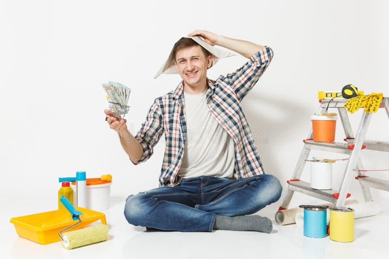 Glücklicher Mann im Zeitungshut hält Bündel Dollar, Bargeld Instrumente für die Erneuerungswohnung lokalisiert auf Weiß stockfotos