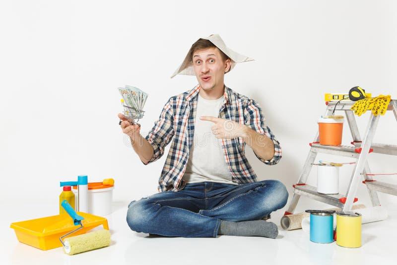 Glücklicher Mann im Zeitungshut hält Bündel Dollar, Bargeld Instrumente für die Erneuerungswohnung lokalisiert auf Weiß lizenzfreies stockfoto