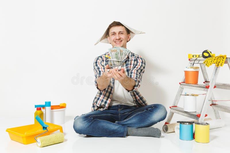 Glücklicher Mann im Zeitungshut hält Bündel Dollar, Bargeld Instrumente für die Erneuerungswohnung lokalisiert auf Weiß stockbilder