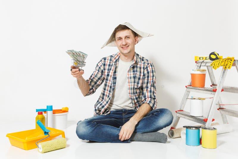 Glücklicher Mann im Zeitungshut hält Bündel Dollar, Bargeld Instrumente für die Erneuerungswohnung lokalisiert auf Weiß stockbild