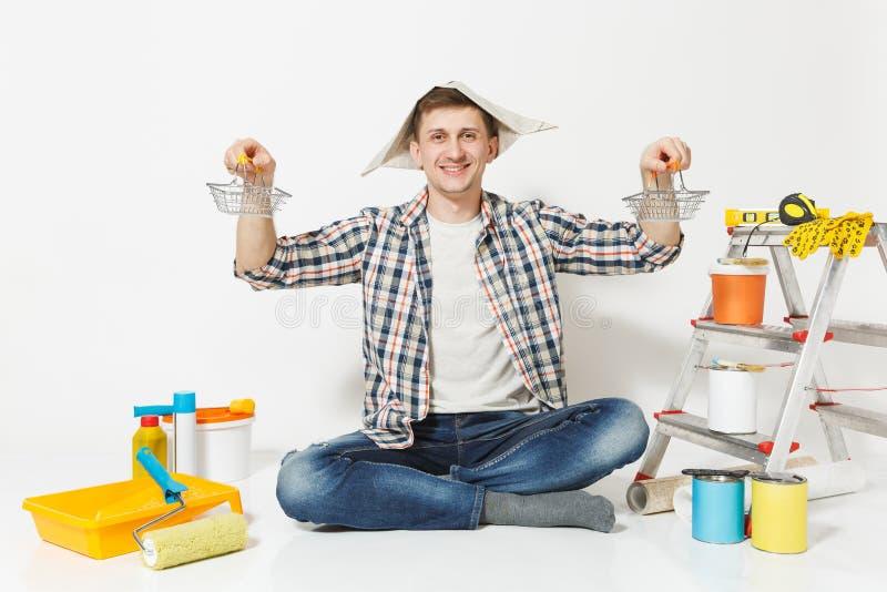 Glücklicher Mann im Zeitungshut hält Supermarktmetalllebensmittelgeschäftkörbe für den Einkauf Instrumente für Erneuerungswohnung stockfotos
