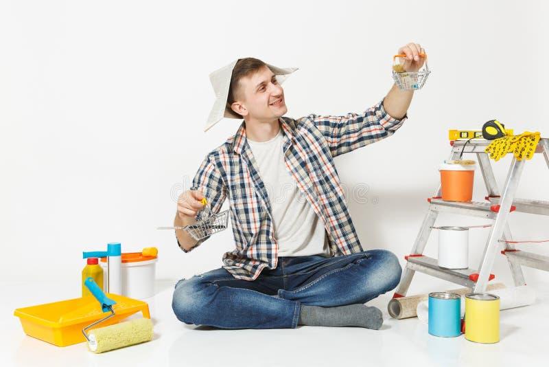 Glücklicher Mann im Zeitungshut hält Supermarktmetalllebensmittelgeschäftkörbe für den Einkauf Instrumente für Erneuerungswohnung stockfotografie