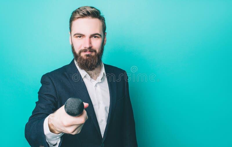 Glücklicher Mann ist stehend und direkt schauend Er hält ein Mikrofon für interwiew Kerl schaut überzeugt lizenzfreie stockbilder