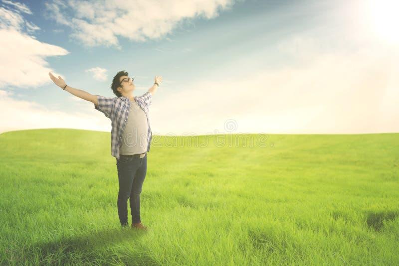 Glücklicher Mann mit breitem offenem genießendem Frühling der Arme auf grüner Wiese lizenzfreie stockfotos