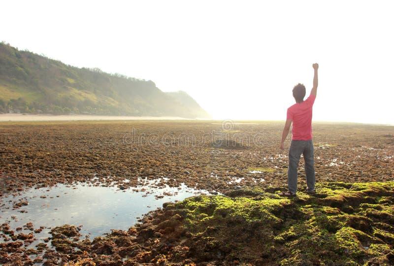 Glücklicher Mann mit den Armen angehoben auf Strand stockfotografie
