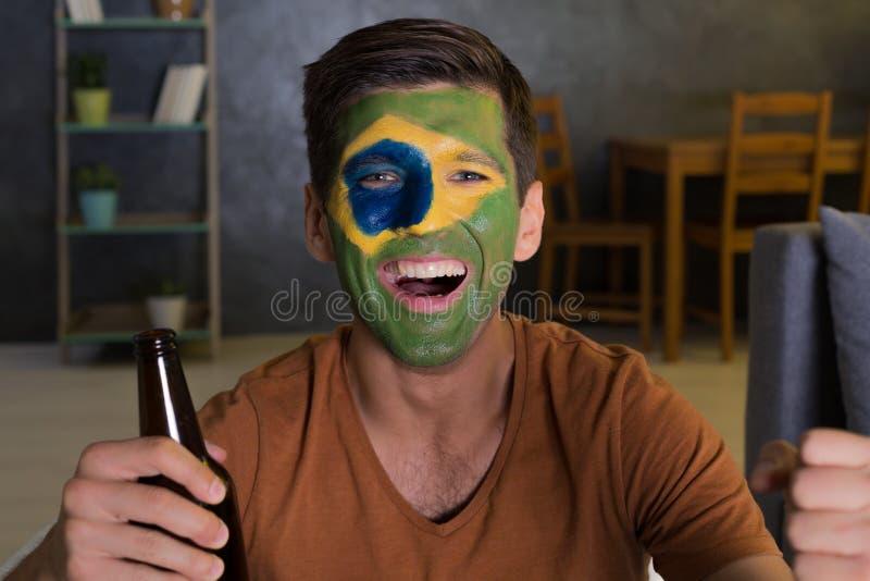Glücklicher Mann mit gemalter Flagge von Brasilien lizenzfreies stockfoto