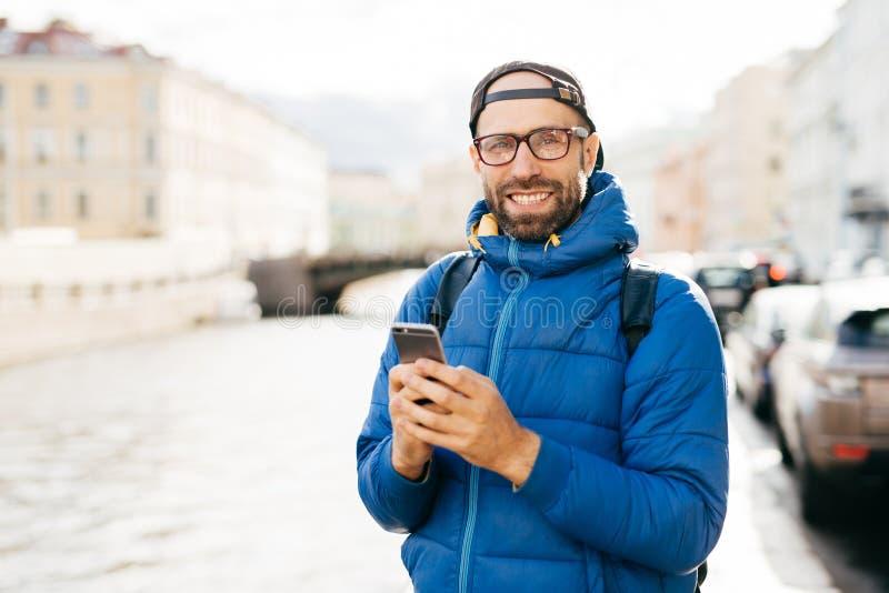Glücklicher Mann mit tragenden Brillen des Bartes kleidete im blauen Anorak an, der Rucksack und beweglich hält, den glücklichen  lizenzfreies stockfoto