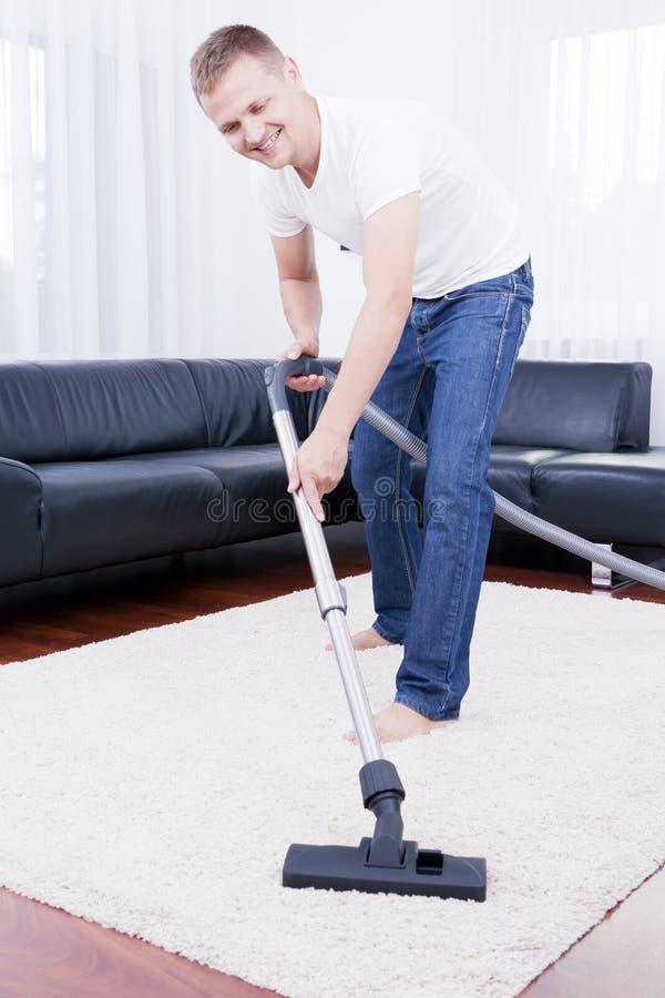 Glücklicher Mann säubert in den modernen Raum mit Vakuum. stockfoto