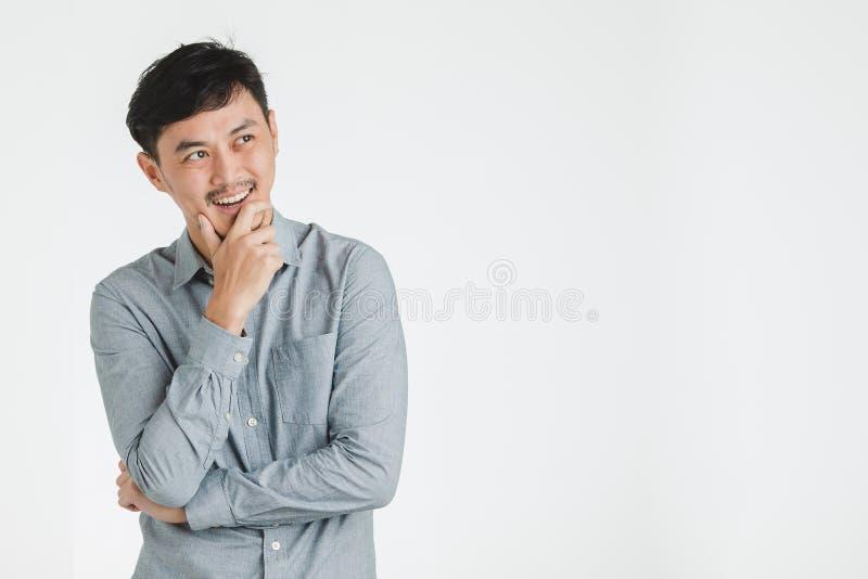 Glücklicher Mann scheint Denken oder Wunsch für einige gute Sachen stockbild