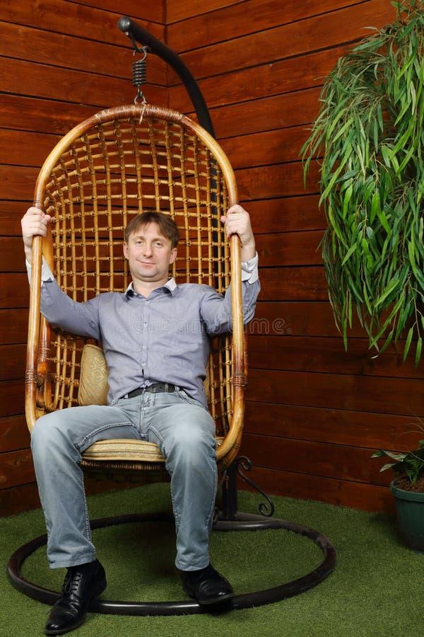 Glücklicher Mann sitzt im hängenden Weidenstuhl stockbild