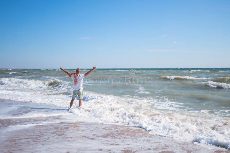 Glücklicher Mann steht auf dem Strand in der Brandungslinie, mit ausgestrecktem AR stockbilder