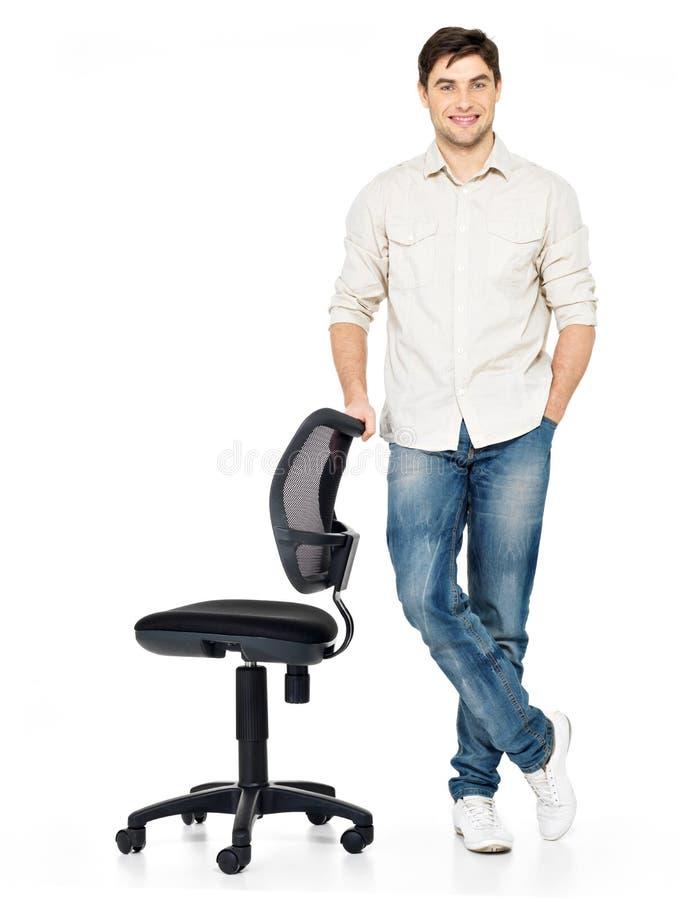Glücklicher Mann steht nahe dem Bürostuhl stockfotos