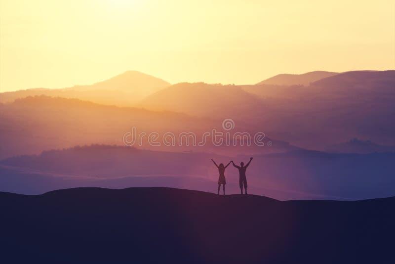 Glücklicher Mann und Frau, die auf einem Hügel steht lizenzfreie abbildung